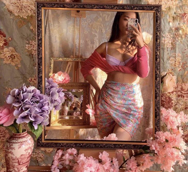 Chica morena de pelo largo con falda floreada y suéter rosa se toma selfie frente al espejo