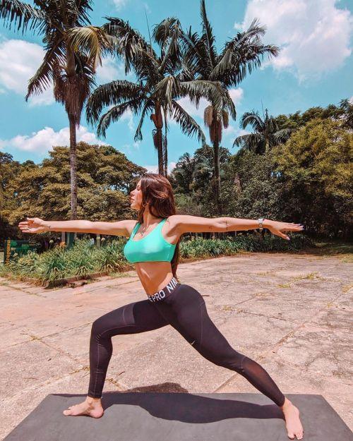 Chica fitness con top verde y pantalón negro hace yoga