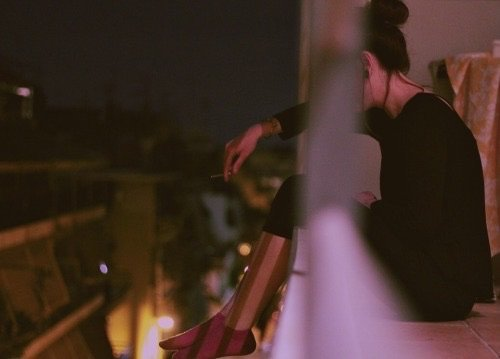 Chica triste con cabello en chongo se sienta en la orilla d eun edificio
