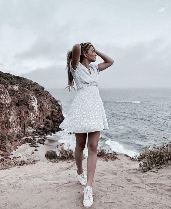 Chica rubia con vestido de lores se toma el cabello mientras posa en la playa