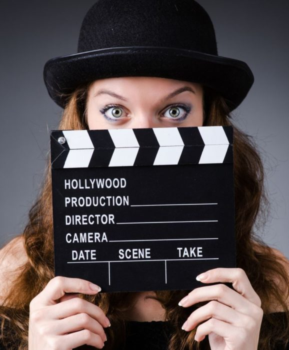 Chica cubriendo su rostro con una claqueta de cine