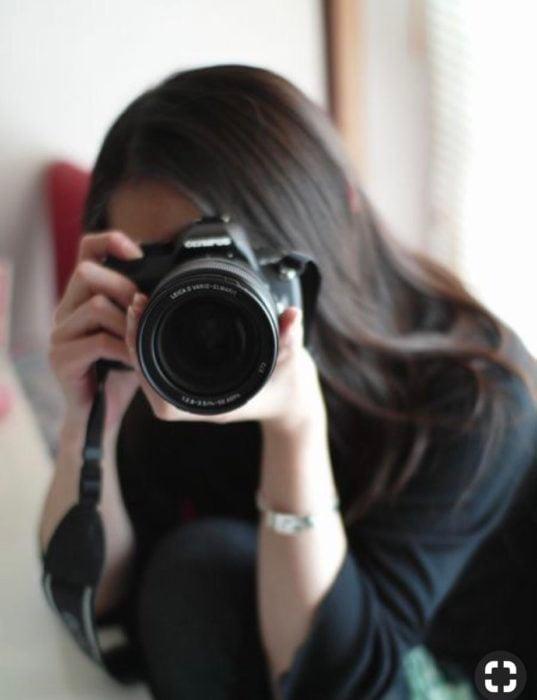 Chica sosteniendo una cámara digital