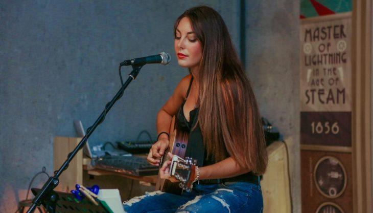 Chica tocando la guitarra y cantando