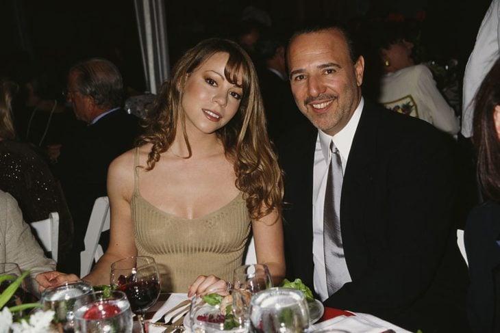 Tommy Motola sentado junto a Mariah Carey durante una cena