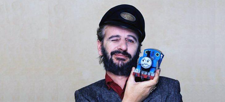 Ringo Star sosteniendo en su hombro una locomotora de Thomas