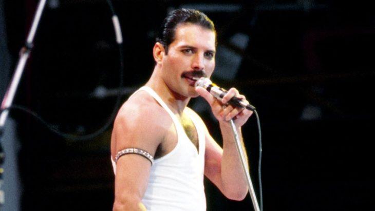 Freddie Mercury sosteniendo un micrófono mientras canta