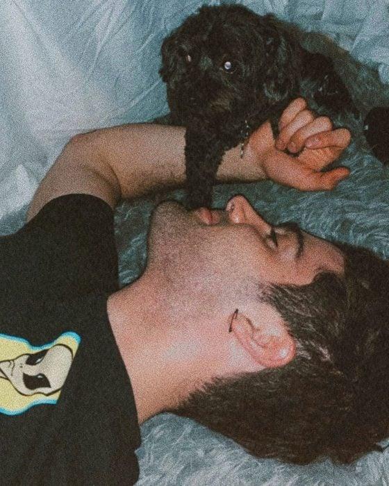 Max Ehrich recostado junto a su perro