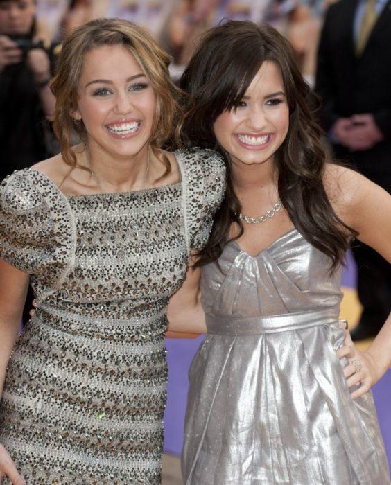 Demi Lovato y Miley Cyrus abrazadas durante una alfombra roja