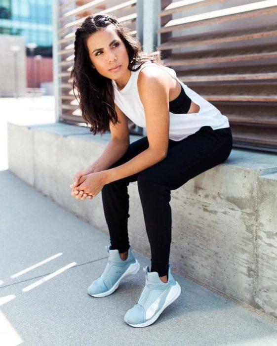 Chica sentada usando ropa deportiva