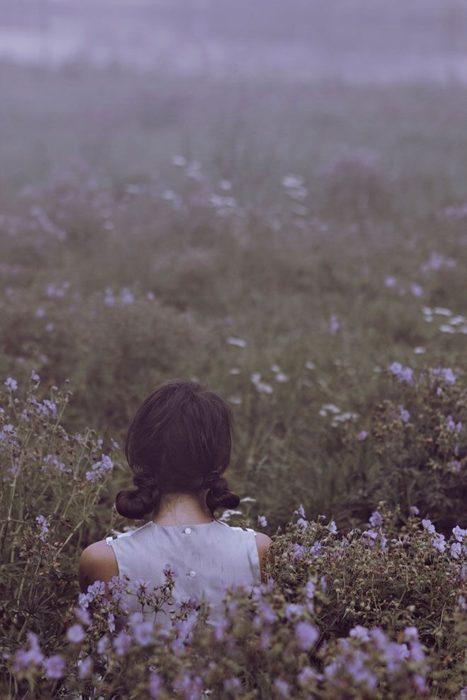 Chica con cabello corto de espladas mira un campo de lavanda