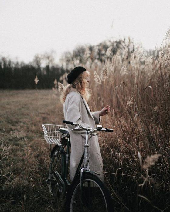 Chica con gorrito negro y una bici observa el campo