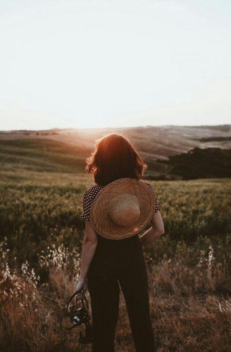 Chica con cabello corto y un sombrero en la espalda mira el atardecer