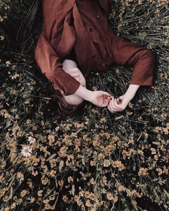 Chica con blusa roja acostada en el pasto