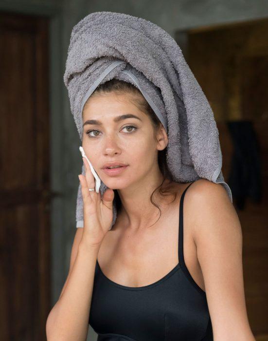 Chica aplicando tónico en su piel