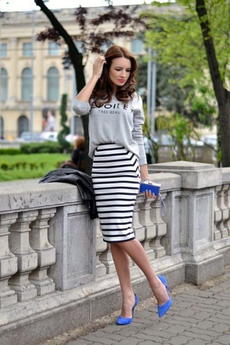Girl touches her hair and wears black and white pencil skirt