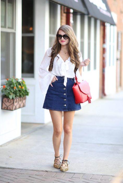 Chica con falda de mezclilla y blusa blanca