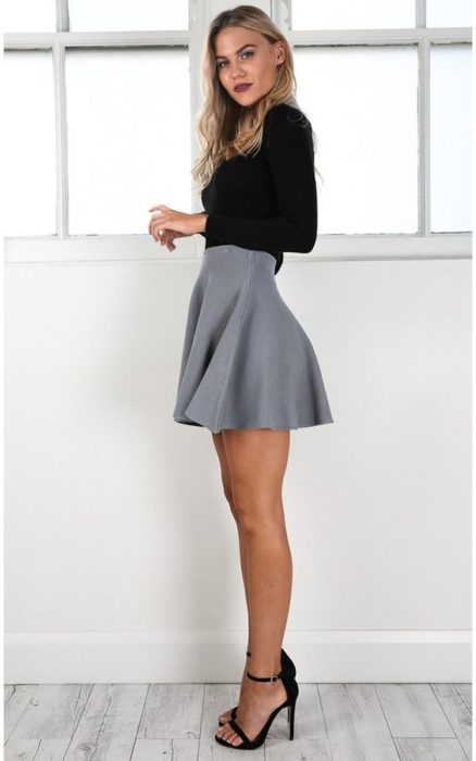 Blonde girl in black blouse and gray round skirt