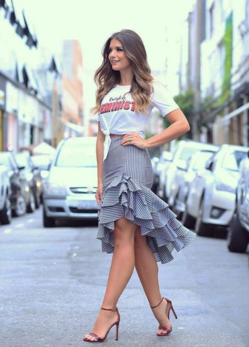 Girl crossing the street in black peplum skirt with white