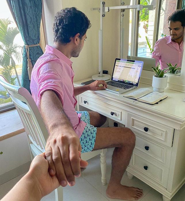 Persona tomando de la mano a su pareja para recrear la fotografía follow me pero en casa
