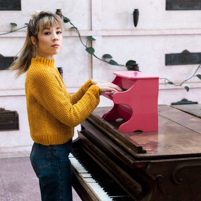 Jennette McCurdy tocando un minipiano en color rosa