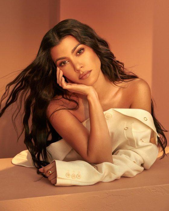 Kourtney Kardashian recargada en su propio brazo llevando una camisa abierta en color blanco