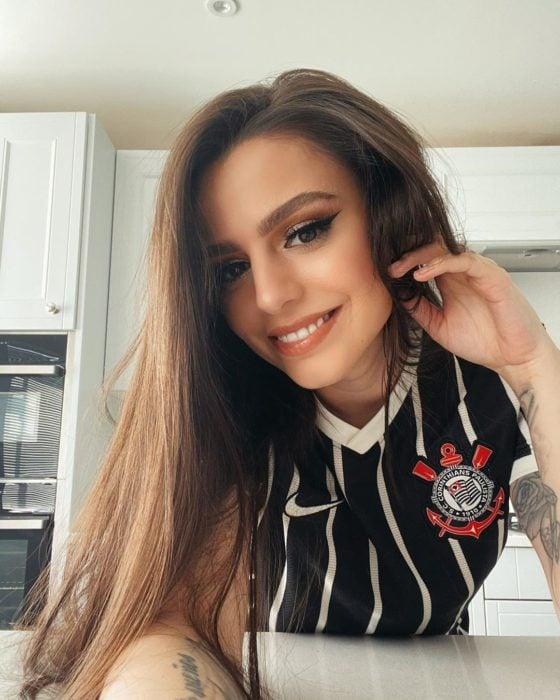 Cher Lloyd recargada en una mesa dentro de una cocina blanca