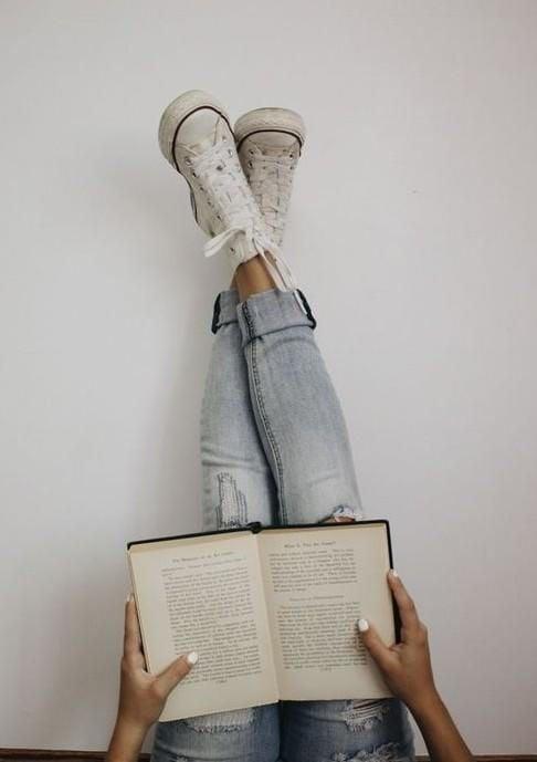 Chica con piernas arriba pegadas a la pared blanca mientras lee un libro
