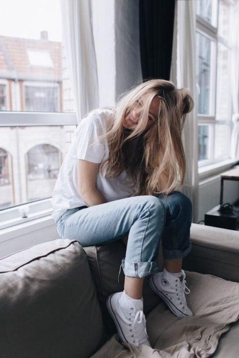 Chica rubia de cabello largo con blusa blanca y jean sentada en un sillón junto a la ventana