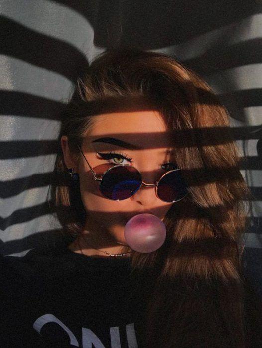 Chica rubia con ojos azules hace bomba de chicle frente a la ventana y los rayos del sol se reflajan en su cara