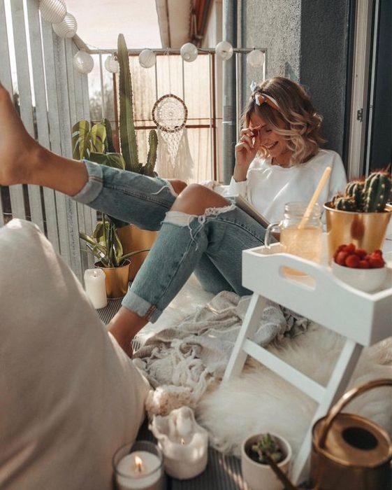Chica sentada en el piso extiende la pierna y se lleva la mano a la cara mientras se ríe