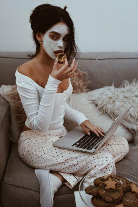 Chica santada en el sillón con su laptop en las piernas usa una mascarilla de arcilla