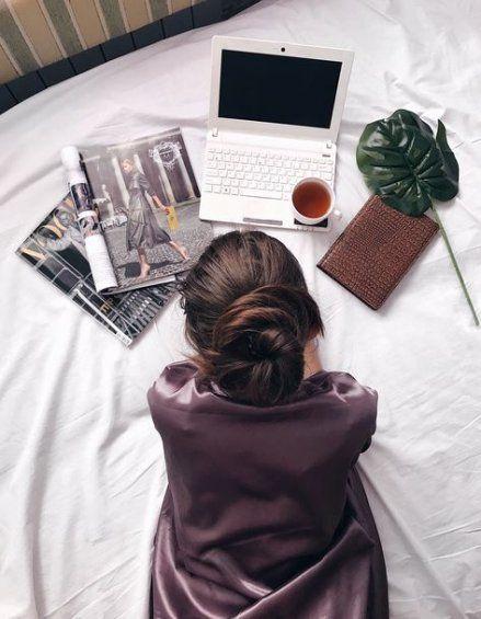 Chica acostada en la cama con revistas, libreta café y una laptop blanca