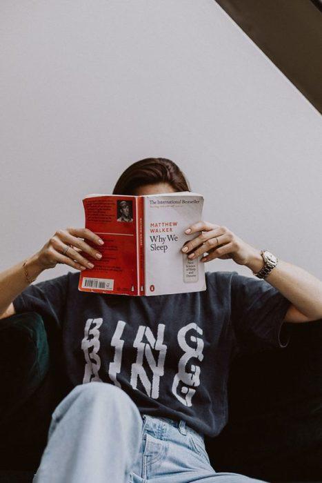 Chica con blusa negra sostiene un libro y se tapa la cara