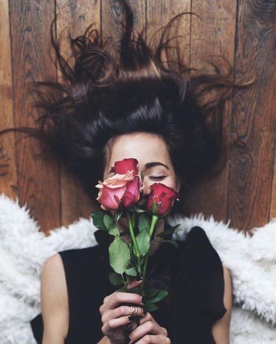 Chica acostada en el piso con el cabello extendido y flores en la casa