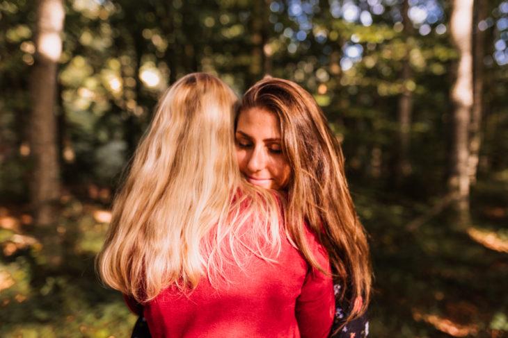 Madre e hija abrazadas mientras están en medio del bosque