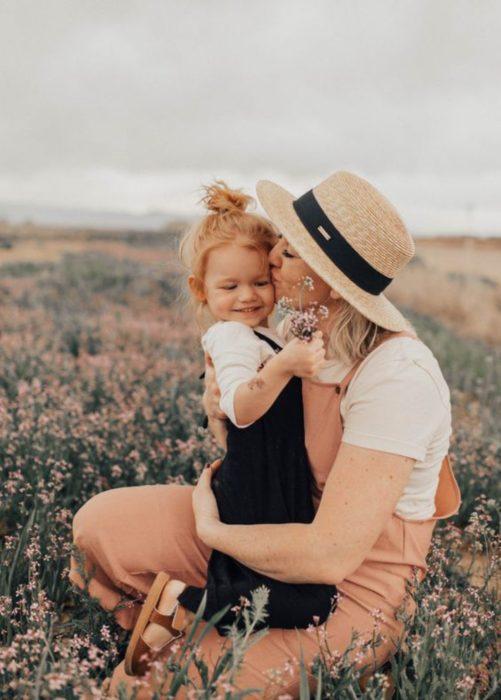 Madre besando a su hija mientras están en medio de un campo