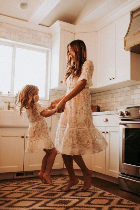 Madre e hija bailando mientras están en la cocina