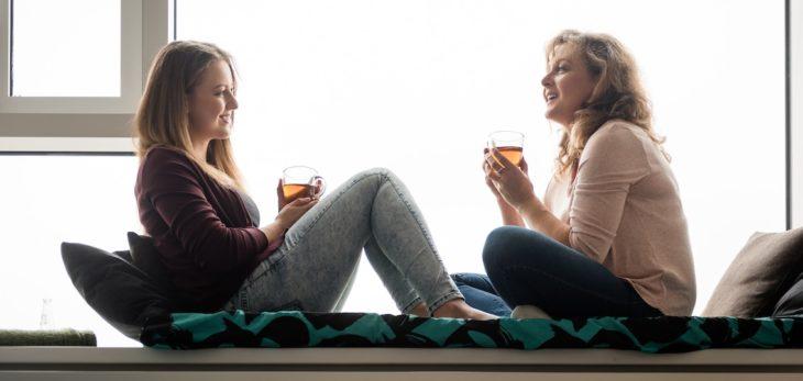 Madre e hija bebiendo te mientras están sentadas en la ventana