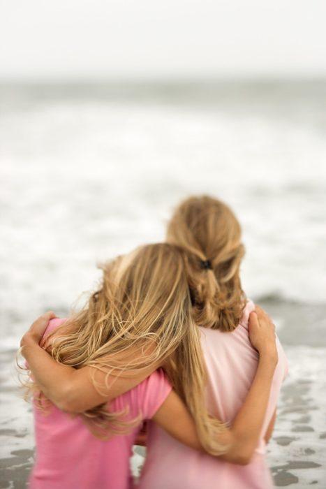 Madre e hija abrazadas mientras están mirando hacia el mar