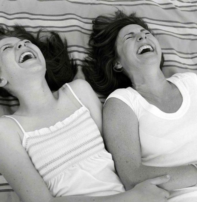 Madre e hija riendo mientras están recostadas en el pasto
