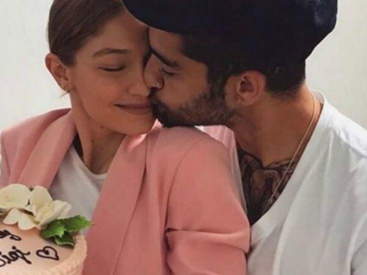 Gigi Hadid y Zayn Malik abrazados, sosteniendo un ramo de flores