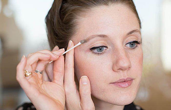 Mujer corrigiendo maquillaje con un hisopo