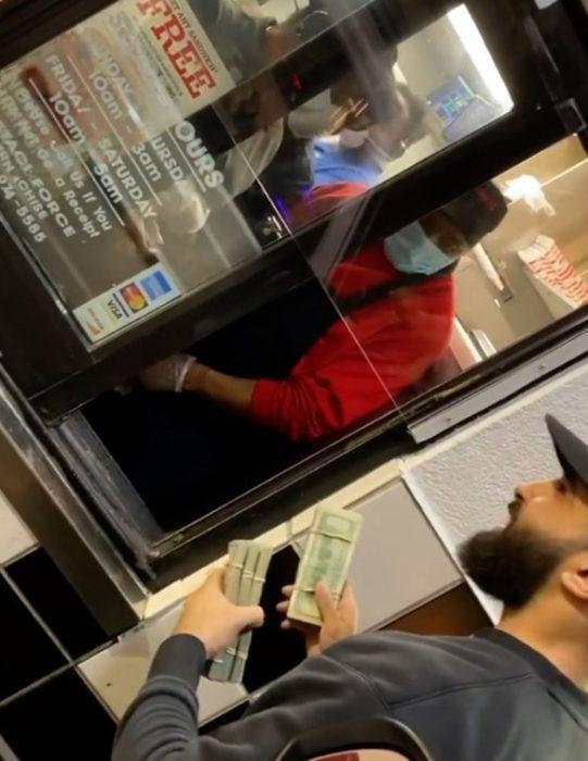 Hombre entrega dinero a empleados de restaurante de comida rápida
