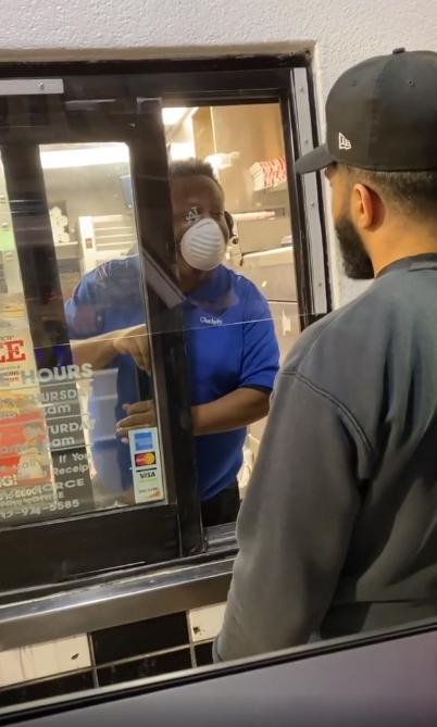 Hombre hablando con un empleado de un restaurante de comida rápida