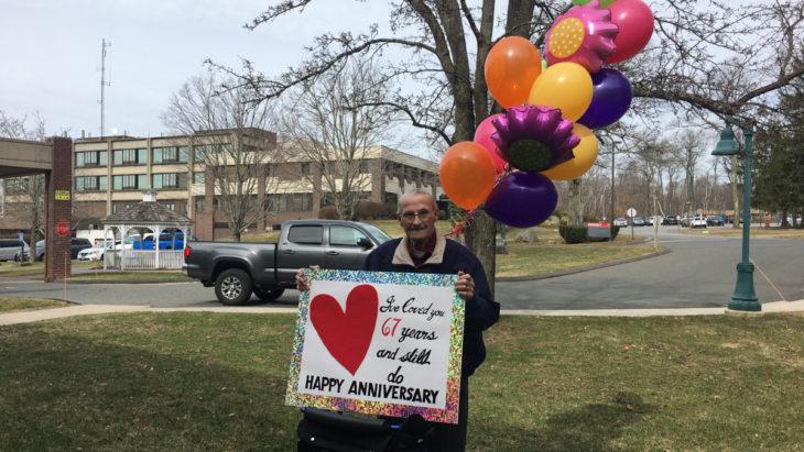 Hombre sentado afuera de un asilo sosteniendo una pancarta para su esposa