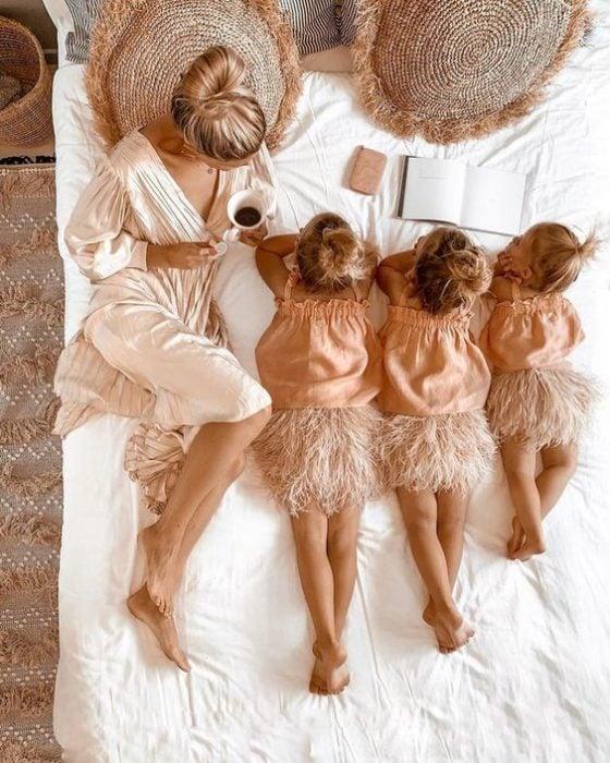 Madre y sus tres hijas recostadas en la cama en una foto cenital