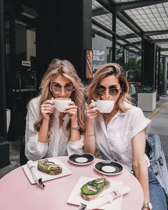 Madre e hija rubias tomando café con gafas de sol