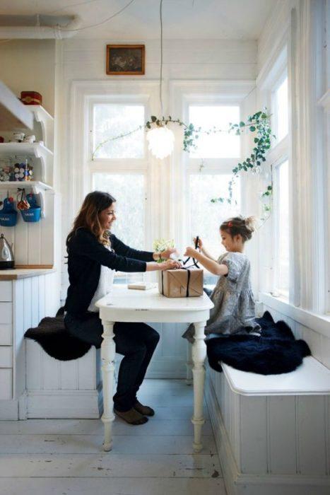 Madre e hija abriendo regalos en la mesa de la cocina