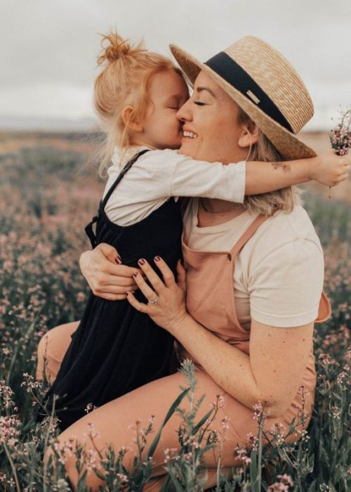 Niña pequeña bes a su mamá en la mejilla en un campo con flores rosas