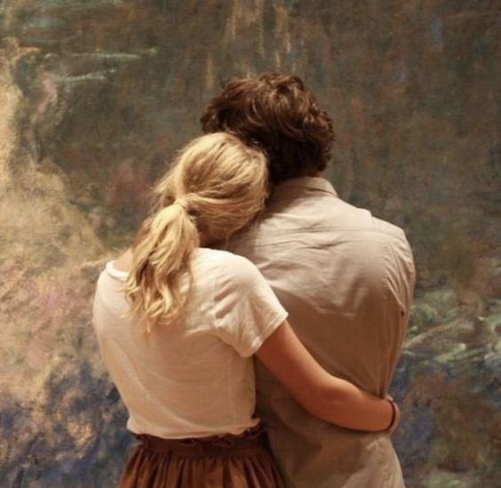 Pareja abrazándose mientras ven pintura